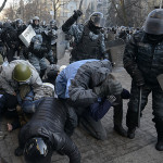 Riot police attack anti-government protesters during clashes in Kiev